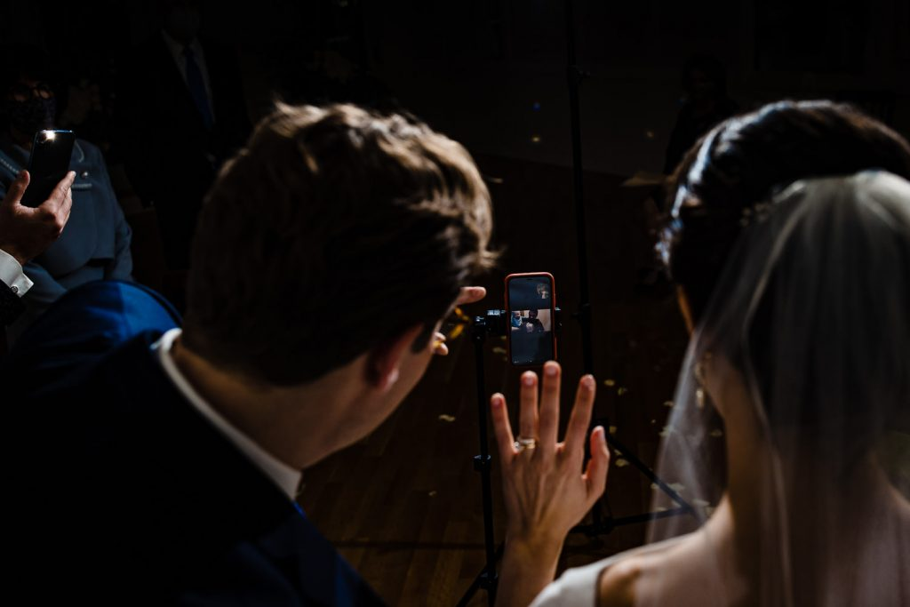 A bride and groom wave to their virtual wedding guests on a cell phone