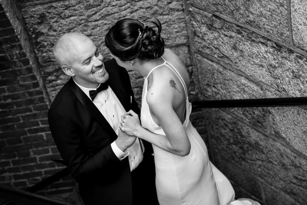 A groom smiles and holds his brides hand as they walk down a stone spiral staircase