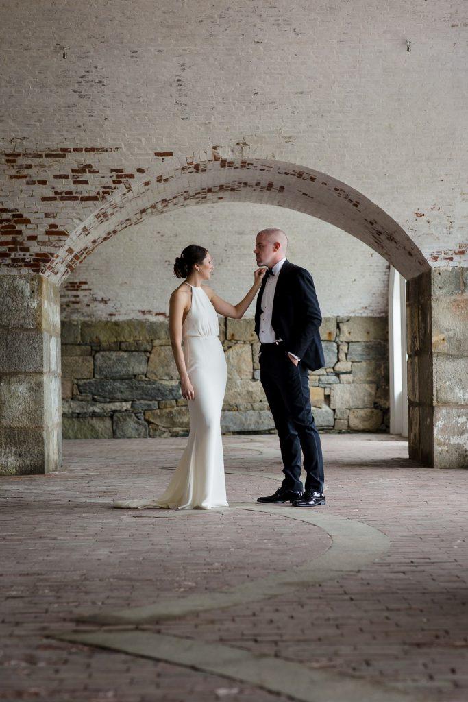 A bride adjusts her grooms tie under a brick archway at a fort adams wedding in Newport, RI