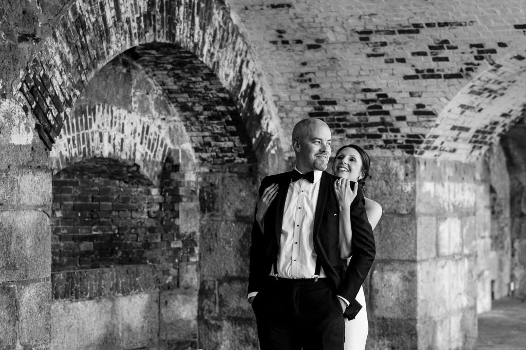 A bride hugs her groom from behind in an old brick arched building