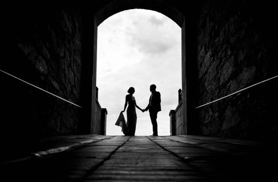 A silhouette photo of a bride and groom holding hands inside a tunnel at a Fort Adams wedding by Brave Hearts Photography