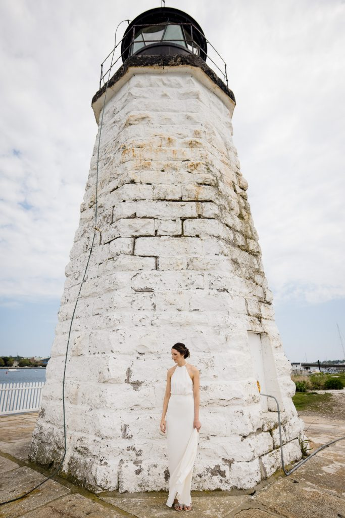 A bride stands by the Newport Harbor lighthouse as she waits for her groom