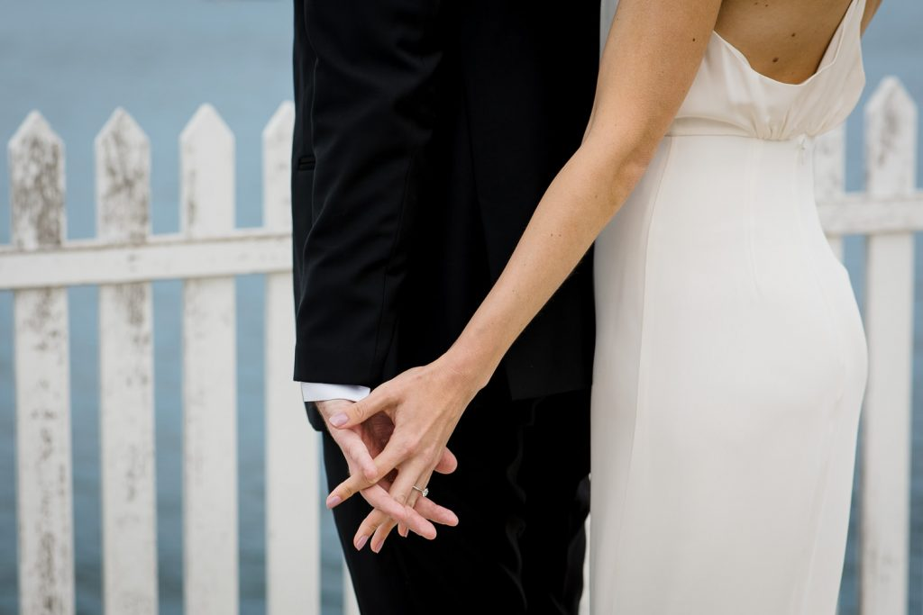 A bride and groom touch hands before seeing each other during their first look