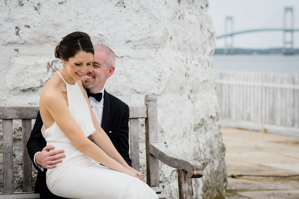 A bride sits on her grooms lap and they smile with the newport bride in the background