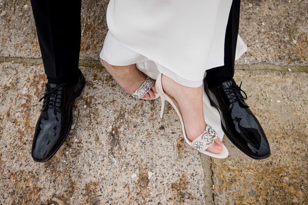 A brides sparkly shoes entertwined with her grooms shiny dress shoes