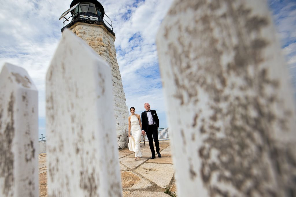 A bride and groom walk hand in hand by the Newport Harbor lighthouse near Gurney's Resort wedding venue in Newport, RI