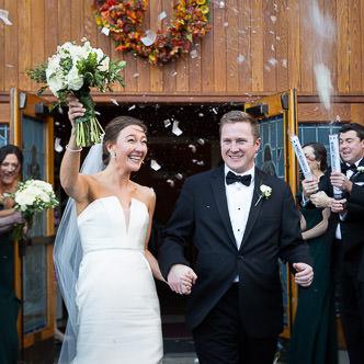 A bride and groom exit their church wedding through confetti canons