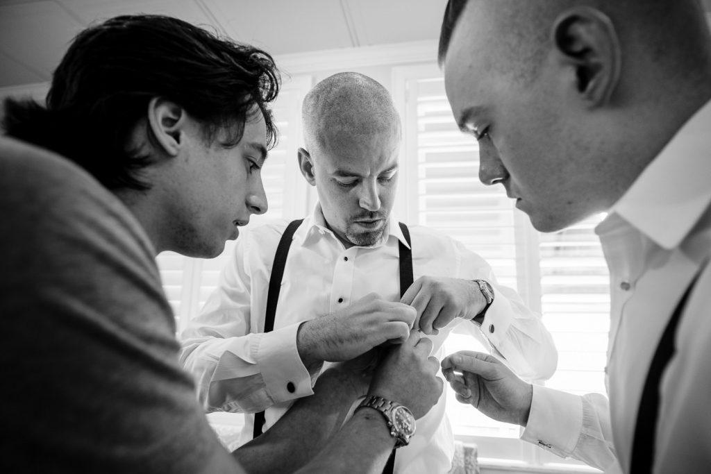Two guys help a groom adjust his suspenders