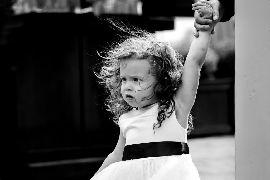A flower girl's curly hair blows in the wind as her hand is held