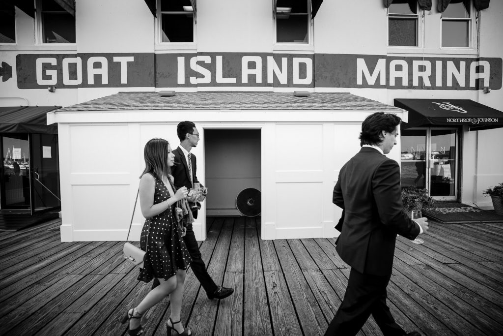 Wedding guests walk by Goat Island Marina sign to a wedding at regatta place