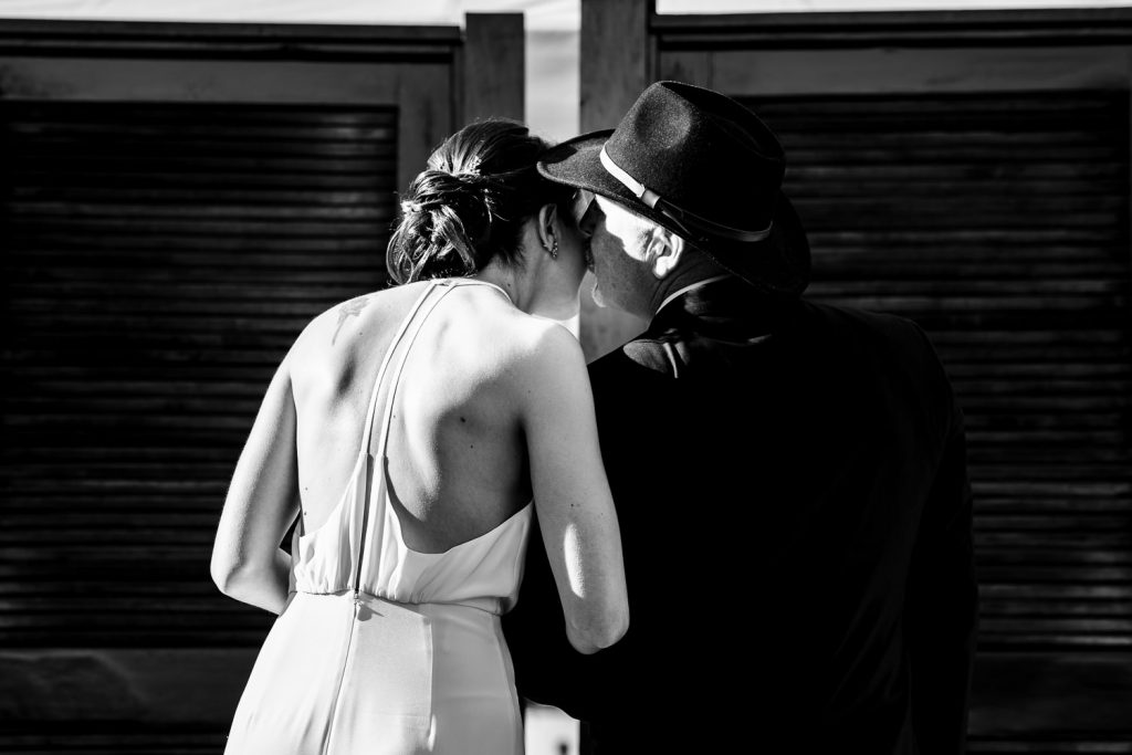 The father of the bride kisses his daughter behind a screen just before it opens and they walk down the aisle