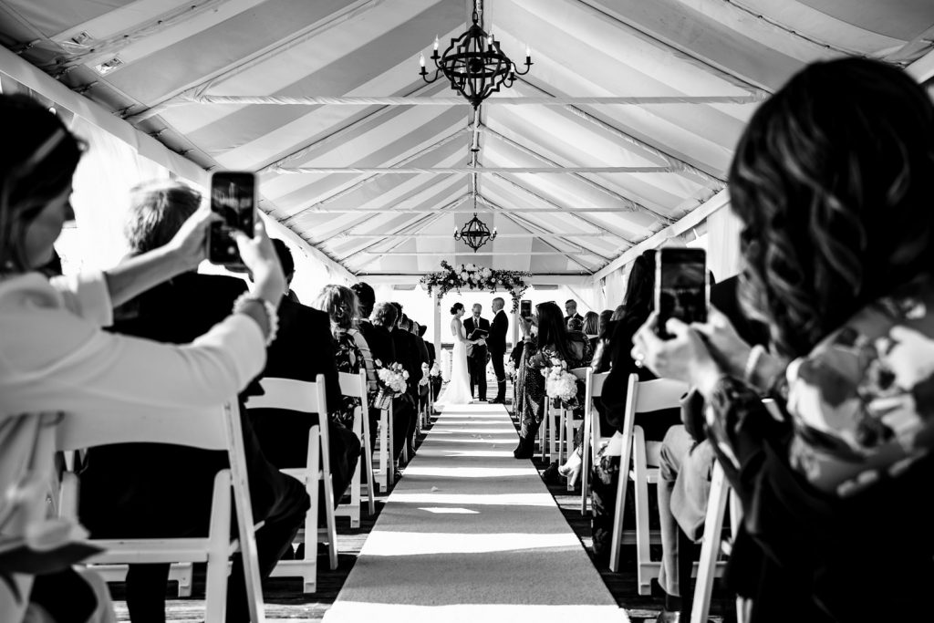 Two wedding guests in the aisle hold out their photos to take a photo of the bride and groom at the alter getting married