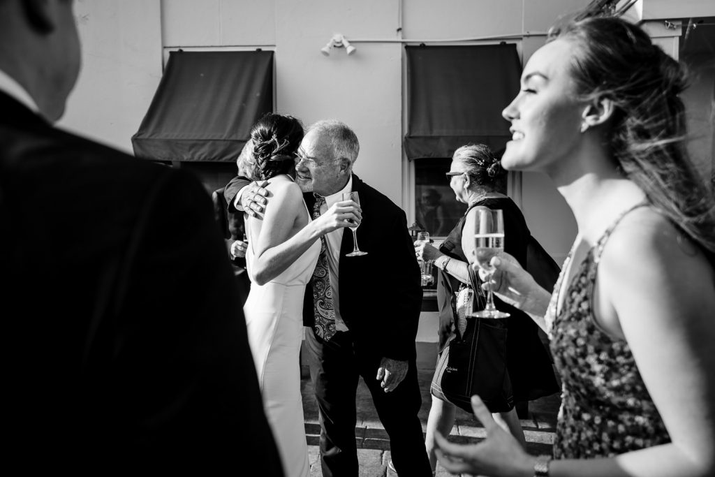 A bride holds champagne and hugs a wedding guest
