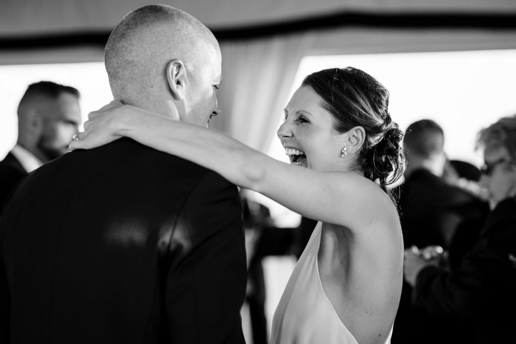 The bride laughs as she dances with her groom