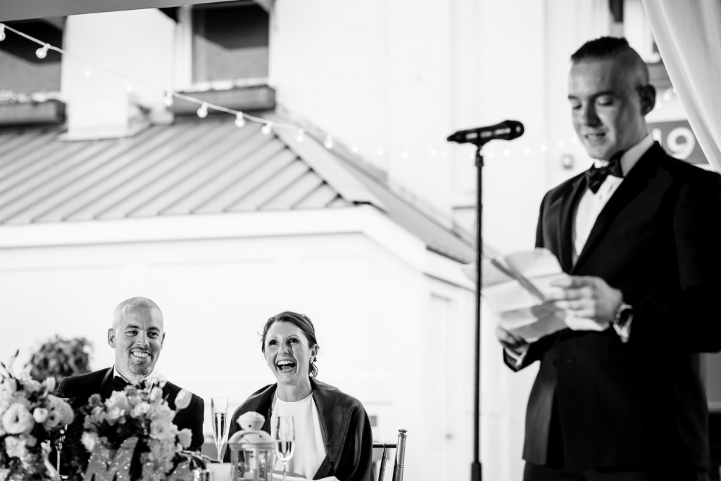 The bride and groom laugh as they listen to the best mans speech at their regatta place wedding