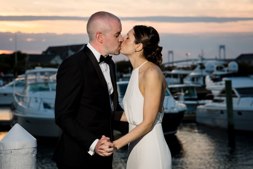 A bride and groom kiss at sunset with the newport bridge in the background