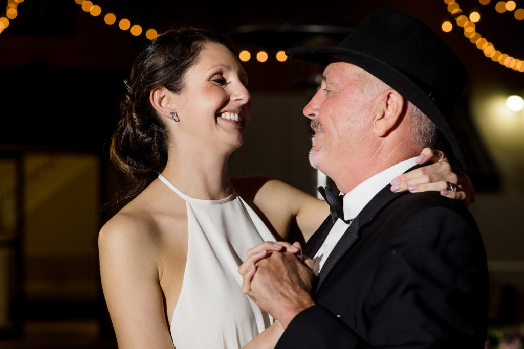 A bride dances with her father who is wearing a black cowboy hat at Regatta Place in newport, RI