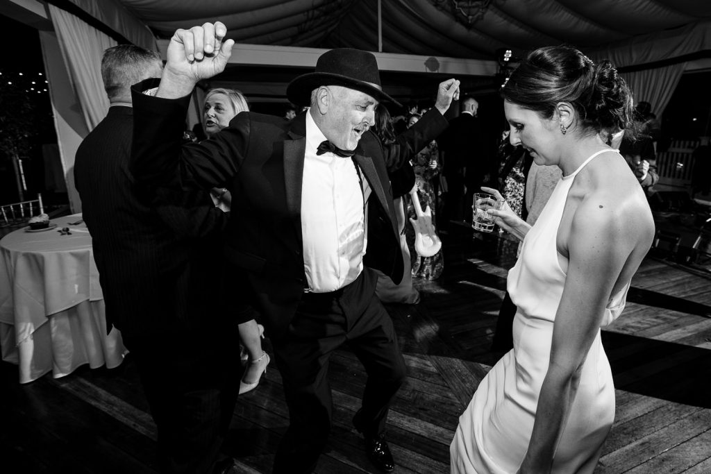 The bride dances at her wedding with her cowboy hat wearing father