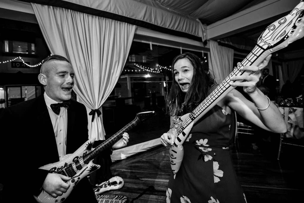 Wedding guests play inflatable guitars during a wedding reception