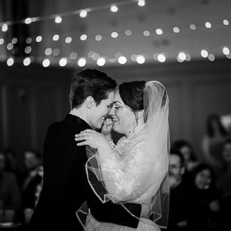 Two brides dancing under a string of lights at their westport ct wedding