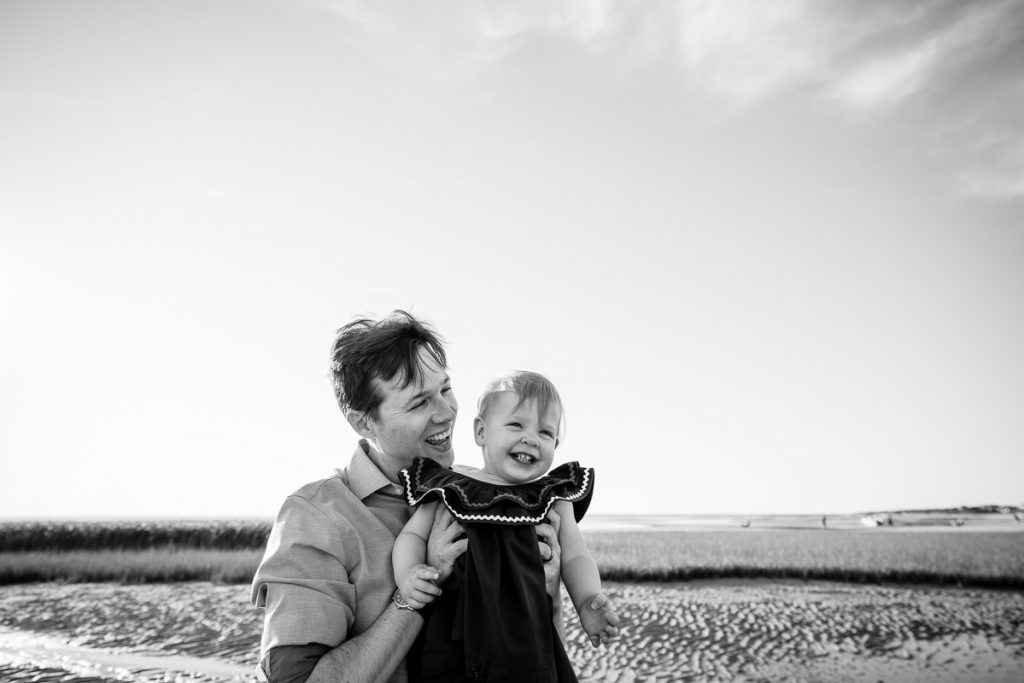 A father and his toddler daughter laugh on the beach during their eastham family photo session on first encounter beach by brave hearts photography