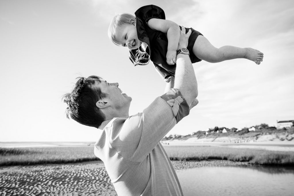 A father holds his laughing toddler daughter up in the air