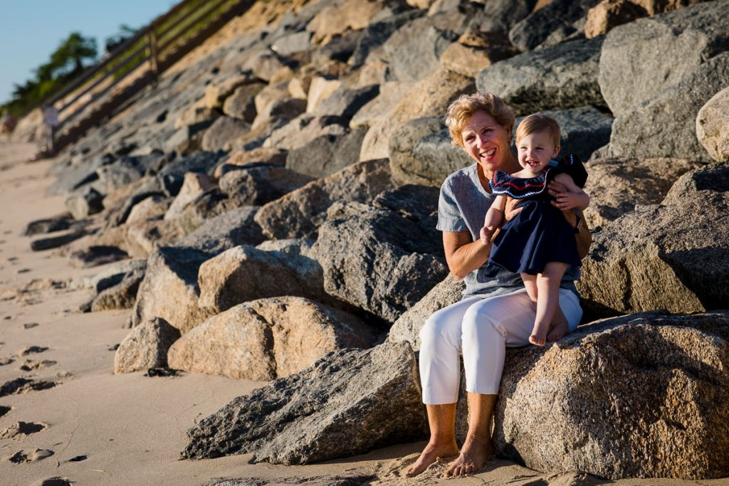 A grandmother and her toddler grandaughter sit on a rock embankment on first encounter beach