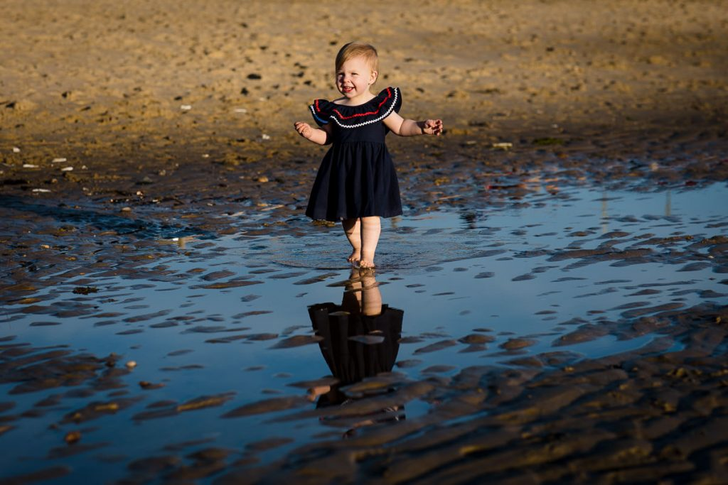 A little girl walks through a tidal pool with her reflection below during an eastham family photo session