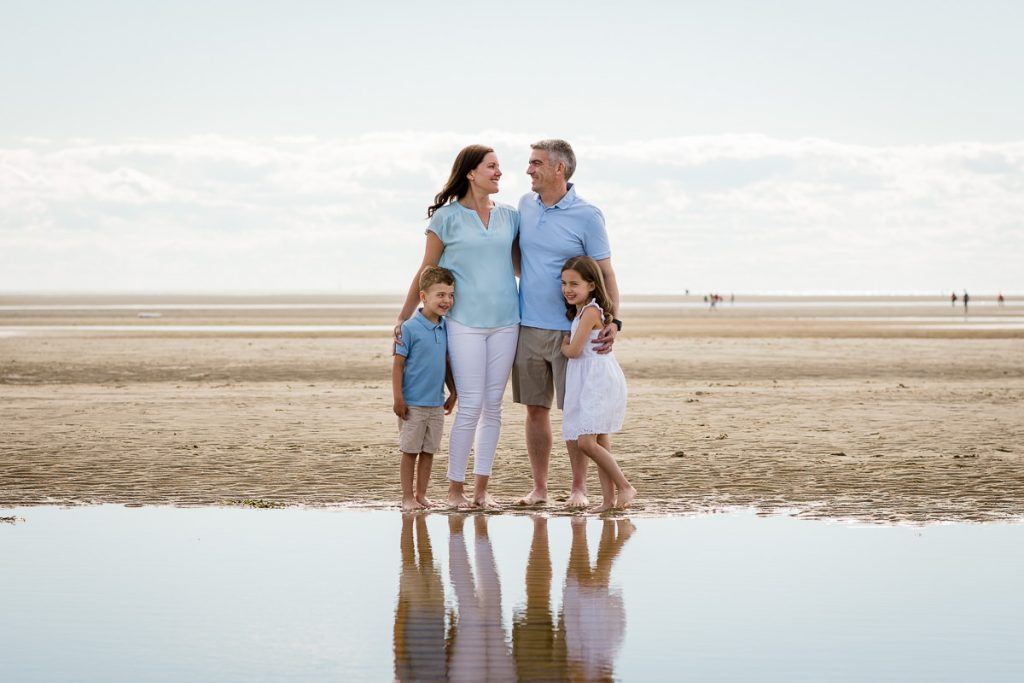 A family stands by a tidal pool during their eastham family photo session on first encounter beach