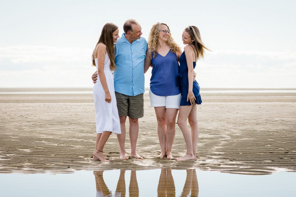 A family on the beach look at one of their daughters