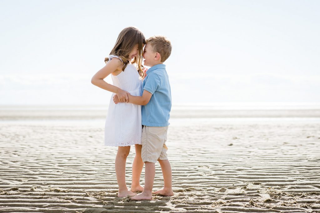 A little girl and boy hug on the beach during their eastham family photo session at first encounter beach
