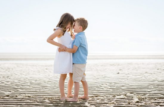 A little girl in a white dress hugs her little brother in a blue shirt on first encounter beach