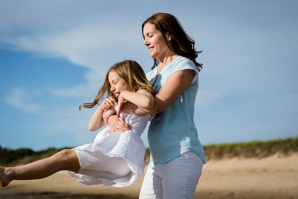 A mom wearing a blue shirt swings her daughter around on the beach