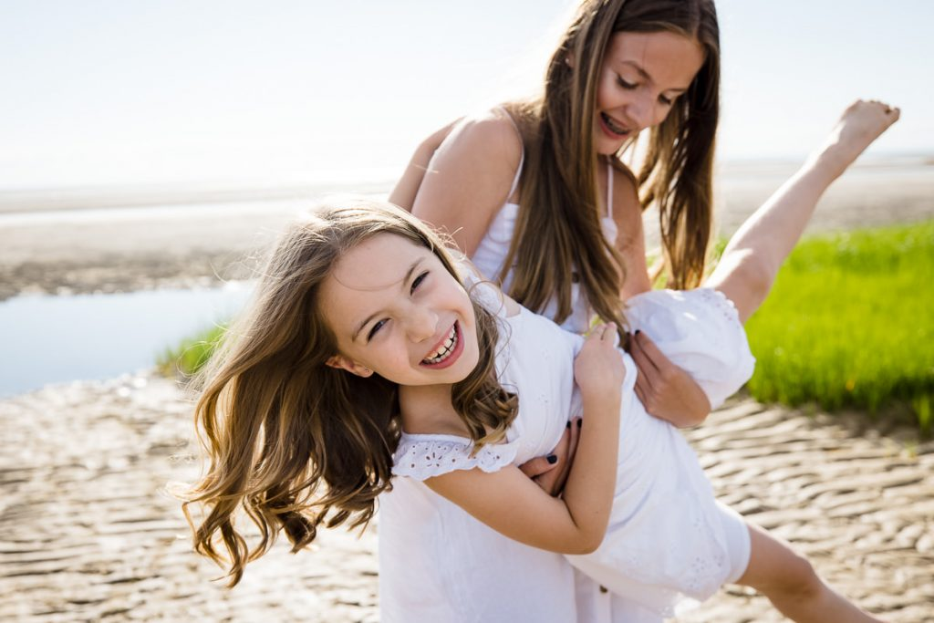 A girl in a white dress swings a little girl around on the beach